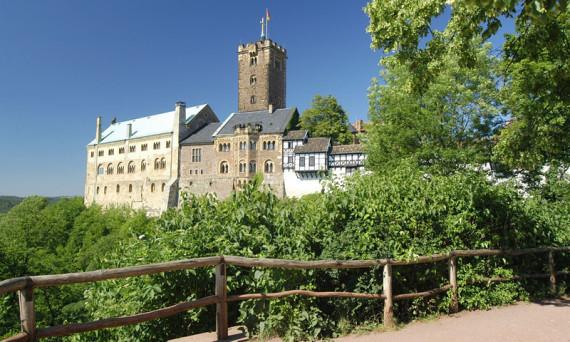 Ein Augenschmauss für jeden Ahnenforscher: man sieht die Wartburg. In der Bildmitte der Turm, davoer in Ringform 4-stöckige Gebäude. Im Vodergrund Wald und rechts im Bild ist ein Baum. Blauer Himmel.