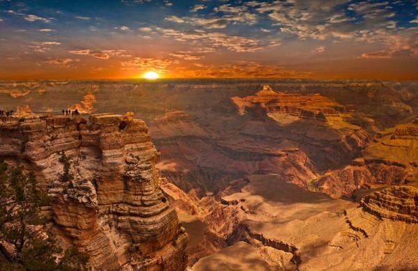 Ein Ahnenforscher-Hobby: die USA. Man sieht den Sonnenaufgang über dem Grand Canyon. Man sieht direkt in die Sonne, der Himmel ist blau mit weißen Wolken, am Horizin auch rot. Der Canyon ist rötlich.