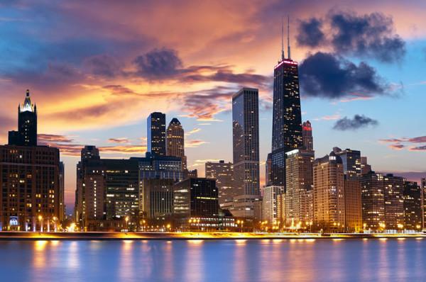 Ein Ahnenforscher-Hobby: die USA. Das Bild zeigt Chicago, die Skyline, vom Wasser aus, in der Abenddämmerung. Die Hochhäuser haben die Lichter bereits an. Es ist schönes Wetter, am Himmel sind Wolken.