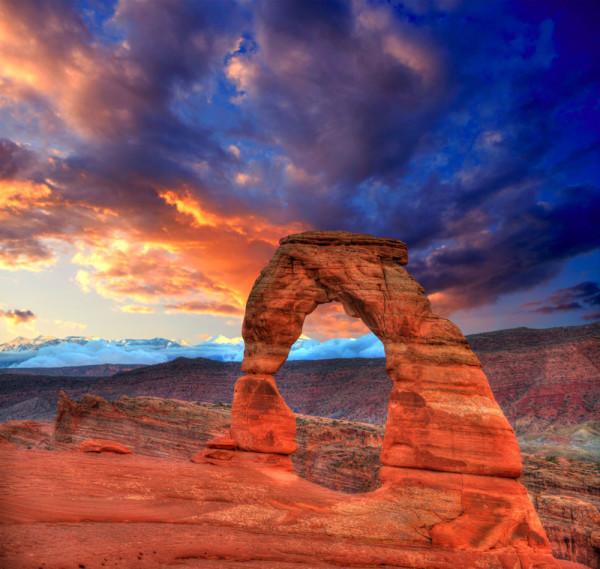 Ein Ahnenforscher-Hobby: die USA. In einem der Nationalparks ist es Abenddämmerung, man sieht noch die Wolken beleuchtet und eine riesige Natursteinbrücke. Alle Farbtöne des Gebirges sind rötlich.