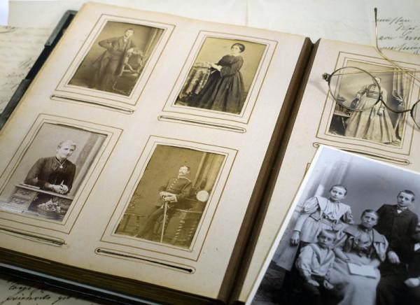 Das Bild zur Ahnenforschung, bei der ein Ahnenforscher nicht helfen kann: man sieht ein Fotoalbum mit einer Seite und vier alten Fotos links. Rechts liegt auf der Seite ein weiteres Bild + eine Brille