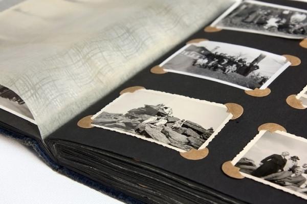 Zur Thematik Ahnenforschung sieht man ein altes Fotoalbum, die rechte Seite. Links isieht man ein Schutzblatt. Die 4 Fotos sind mit großen, runden, beigen Fotoecken auf schwarze Blätter geklebt.