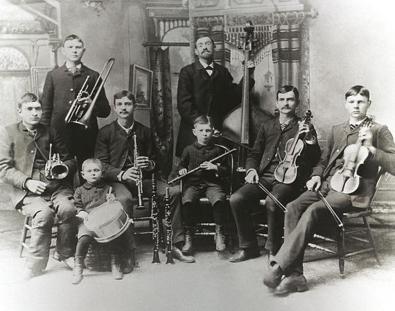 Man sieht auf dem historischen Schwarzweiß-Foto zwei Reihen an Musikern. Vorne sitzen sechs junge Buben, hinten steht ein älterer Junge und der Vater. Alle acht haben ein Instrument. alle sind ernst.