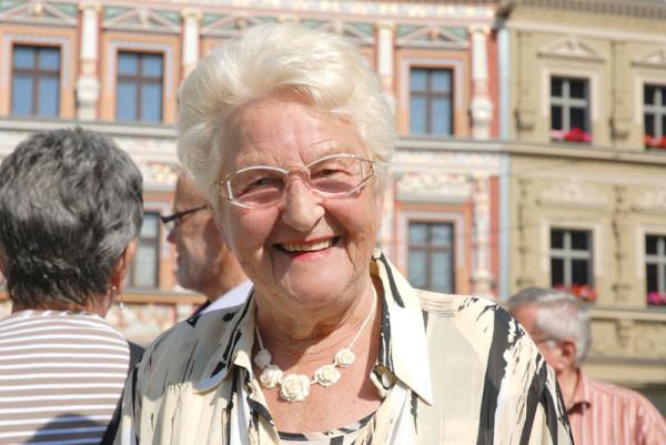 Man sieht eine ältere Dame herzlich zur Kamera lächeln, sie ist weißhaarig und steht vor historischen Gebäuden. Im Hintergrund erkennt man 3 Menschen von der Rückseite. Sie hat beige Kleidung an.