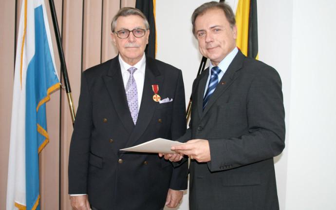 Man sieht zwei Personen bei einer Urkunden-Verleihung. Beide Herren haben dunkle Anzüge und Krawatte an. Hinter den Herren sind zwei Fahnen. Ein der Männer schaut freundlich, Herr Frickel ist ernst.