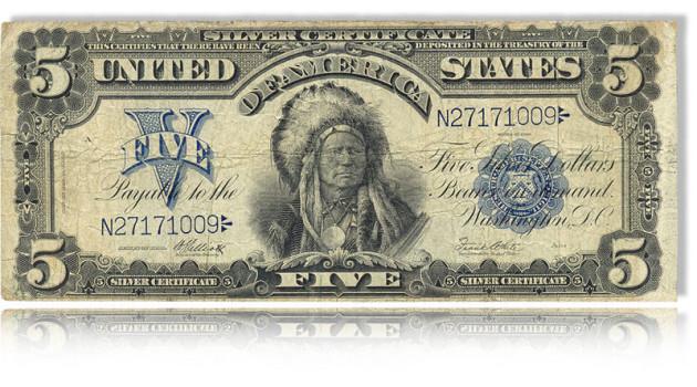 Man sieht einen historischen Dollarschein im Nennwert von 5 Dollar mit einem modernen Spiegel unten an der Illustration. In der Mitte des Scheins ist ein Indianerhäutptling mit großem Federschmuck.