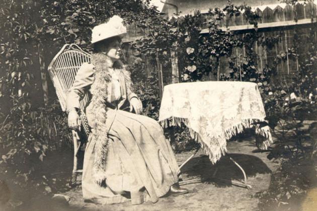 Auf einer historischens chwarzweißen Aufnahme sitzt eine Dame mit Hut an einem Tisch mit Tischdecek im Garten. Sie schaut nicht zur Kamera. Im Hintergurnd ist ein Bretterzaun.