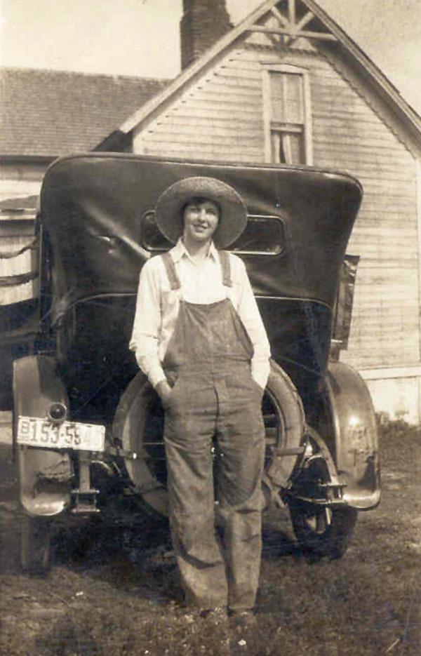 Es ist ein historisches bräunliches Hochformat, auf welchem man eine junge Frau mit großem Hut vor der Rückseite eines Oldtimers sieht. Das Auto steht vor einem Haus. Sie hat die Hände in den Taschen.