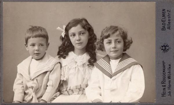 Auf einer historischen bräunlichen Aufnahme sieht man ein gruppe von 3 Kindern , bis zum  Schß fotografiert. In der Mitte ist ein etwas älteres Mädchen. Sie sind festlich angezogen.