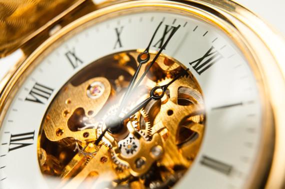 Man sieht das Uhrwerk einer historischen Taschenuhr in den Farben gold und weiß. Der Ausschnitt es sehr startk, man sieht kaum die Hälfte der Uhr. Die Ziffern sind römisch, man sieht beide Zeiger.