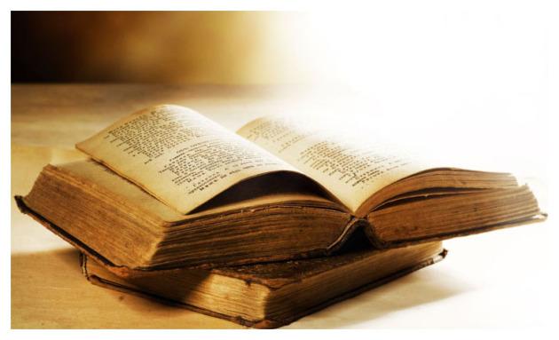 Ein sehr altes historisces Buch liegt aufgeschlagen auf einem weiteren. Es ist eine Collage in Brauntönen und hellem gelblichen Lichtspiel.