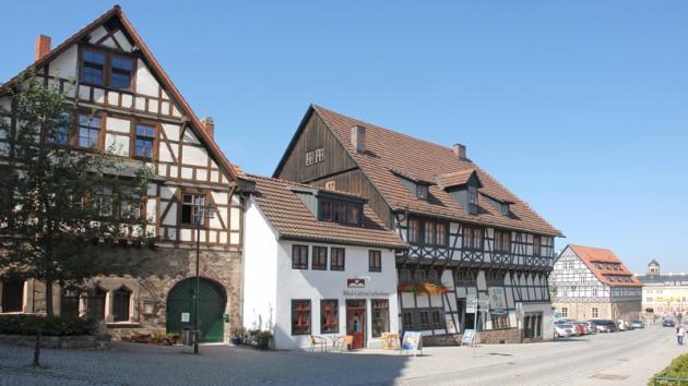 Es ist ein heute aufgenommenes Motiv in Eisneanch. Man sieht drei Fachwerkhäuser, im Hintergrund das Stadtschloss von Eisenach. Der Himmel ist wolkenlos blau und die Sonne bescheint die Häuser.