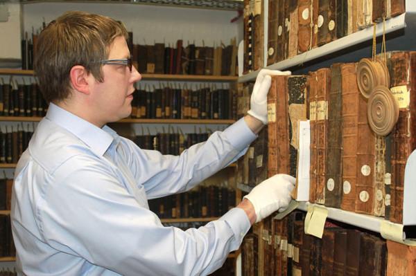 Auf dem Foto sieht man Ahnenforscher Hoske vor einem Regal von vielen, uralten flächenmässig riesigen Büchern. Er hat ein hellblaues Hemd an und weiße Handschuhe, zieht gerade eines der Bücher heraus.